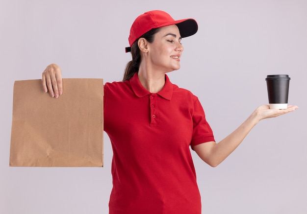 Uśmiechnięta młoda dostawa kobieta w mundurze i czapce trzymająca plastikowy kubek kawy i papierowy pakiet patrząc na filiżankę kawy odizolowaną na białej ścianie