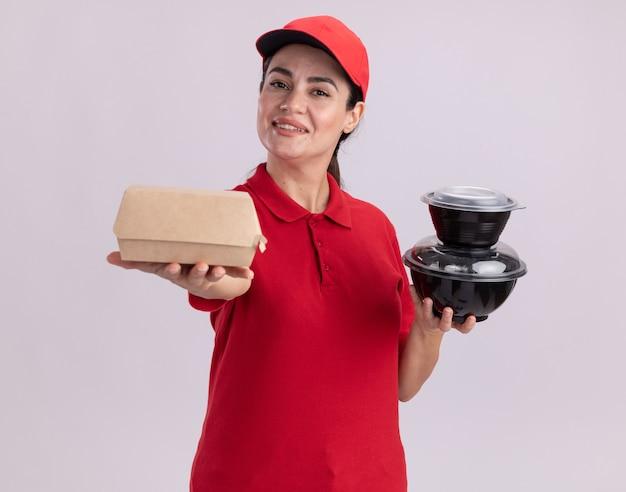 Uśmiechnięta młoda dostawa kobieta w mundurze i czapce wyciąga papierowe opakowanie żywności i trzyma pojemniki na żywność patrząc na przód na białej ścianie
