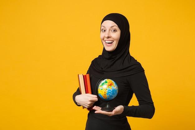 Uśmiechnięta młoda dziewczyna arabskich muzułmańskich studentów w hidżab czarne ubrania trzymać w ręce glob, książki na białym tle na żółtą ścianę portret. koncepcja życia religijnego ludzi.