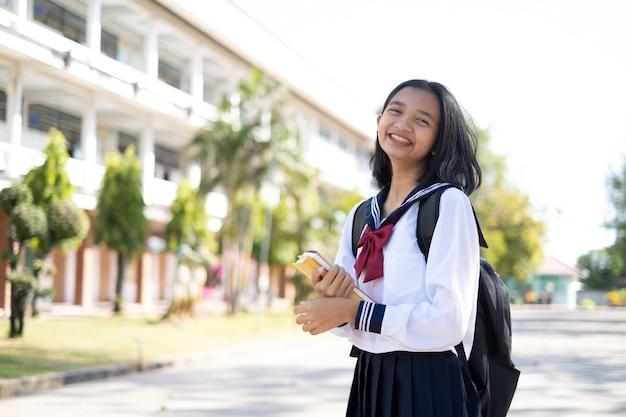 Uśmiechnięta młoda dziewczyna azjatyckich nosi jednolite trzymać książkę stojącą w szkole