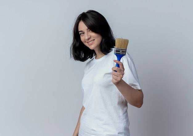 Uśmiechnięta młoda dziewczyna całkiem kaukaski stojąc w widoku profilu i trzymając pędzel na białym tle na białym tle z miejsca kopiowania