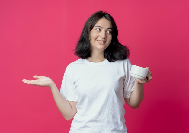 Uśmiechnięta młoda dziewczyna całkiem kaukaski trzymając kubek patrząc z boku i pokazując pustą rękę na białym tle na szkarłatnym tle