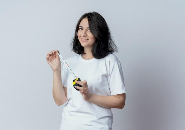 Uśmiechnięta młoda dziewczyna całkiem kaukaski trzymając miernik taśmy na białym tle na białym tle z miejsca na kopię
