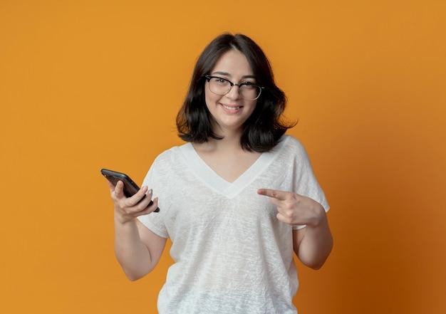 Uśmiechnięta młoda dziewczyna całkiem kaukaski w okularach, trzymając i wskazując na telefon komórkowy na białym tle na pomarańczowym tle z miejsca kopiowania