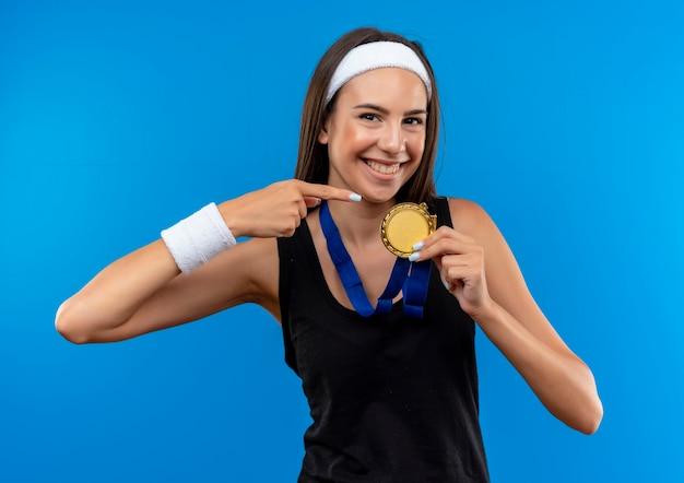 Uśmiechnięta młoda dziewczyna całkiem sportowy noszenie opaski i opaski na głowę i medal na szyi, wskazując na medal na białym tle na niebieskiej przestrzeni