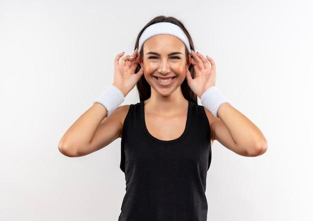 Uśmiechnięta młoda dziewczyna dość sportowy noszenie opaski i nadgarstka robi wielkie uszy na białej przestrzeni