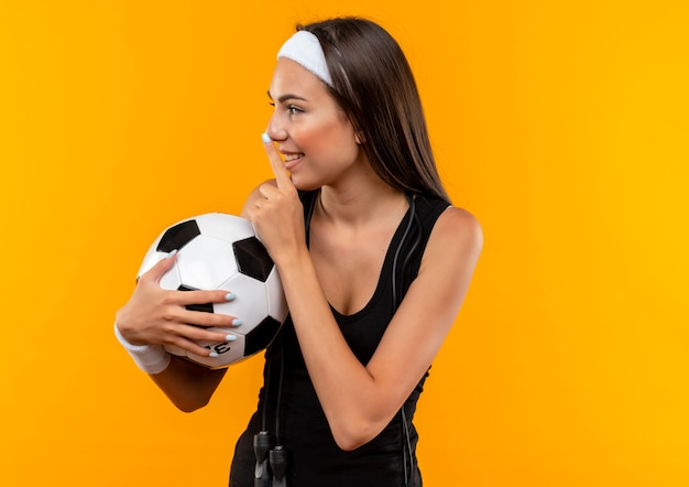 Uśmiechnięta młoda dziewczyna dość sportowy noszenie opaski na głowę i opaskę trzymając piłkę nożną gestem ciszę i patrząc w bok