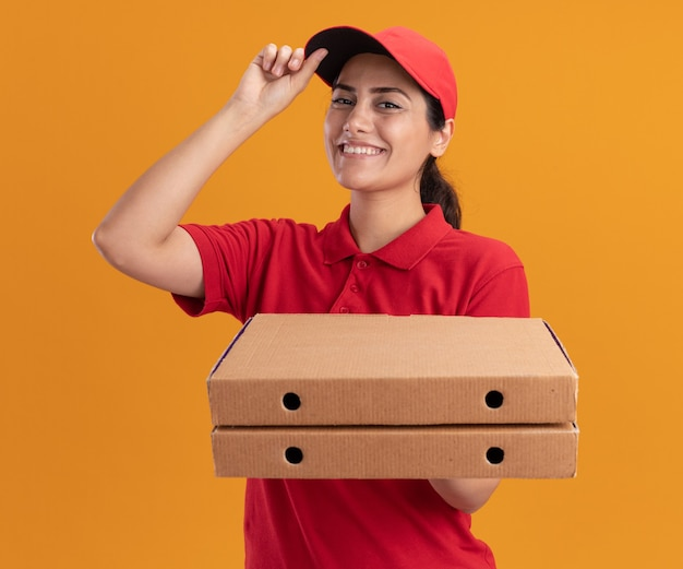 Uśmiechnięta młoda dziewczyna dostawy na sobie mundur i czapkę, trzymając pudełka po pizzy i czapkę na białym tle na pomarańczowej ścianie