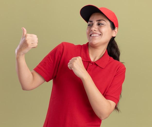 Uśmiechnięta młoda dziewczyna dostawy na sobie mundur z czapką pokazując kciuk do góry na białym tle na oliwkowej ścianie