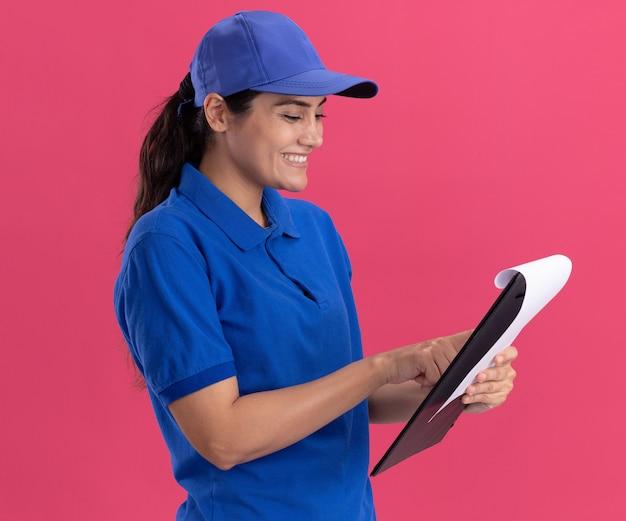 Uśmiechnięta młoda dziewczyna dostawy na sobie mundur z czapką, trzymając i patrząc na schowek na białym tle na różowej ścianie