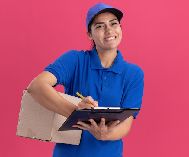 Uśmiechnięta młoda dziewczyna dostawy na sobie mundur z czapką, trzymając pudełko i pisze coś w schowku na białym tle na różowej ścianie