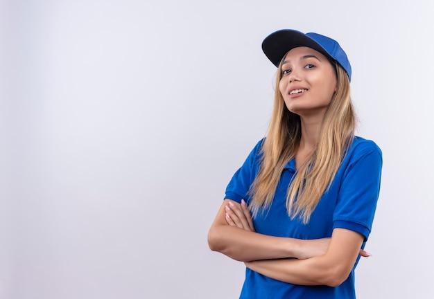 Uśmiechnięta młoda dziewczyna dostawy na sobie niebieski mundur i czapkę skrzyżowania rąk na białym tle