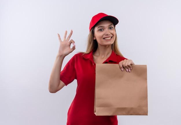 Uśmiechnięta młoda dziewczyna dostawy ubrana w czerwony mundur i czapkę, trzymając papierową torbę i pokazując okey gesrure na białym tle