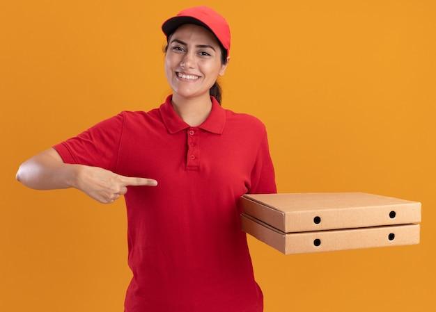 Uśmiechnięta młoda dziewczyna dostawy ubrana w mundur i czapkę trzyma i wskazuje na pudełka po pizzy na białym tle na pomarańczowej ścianie