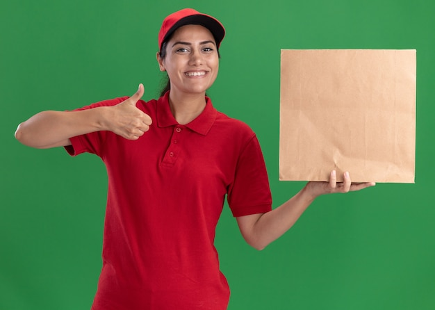 Uśmiechnięta młoda dziewczyna dostawy ubrana w mundur i czapkę trzymając papierowy pakiet żywności pokazując kciuk do góry na białym tle na zielonej ścianie