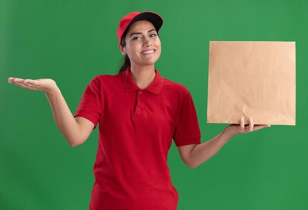 Uśmiechnięta młoda dziewczyna dostawy ubrana w mundur i czapkę trzymając papierowy pakiet żywności, rozkładając rękę na białym tle na zielonej ścianie