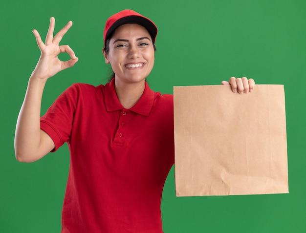 Uśmiechnięta młoda dziewczyna dostawy ubrana w mundur i czapkę trzymając papierowy pakiet żywnościowy pokazujący w porządku gest na białym tle na zielonej ścianie