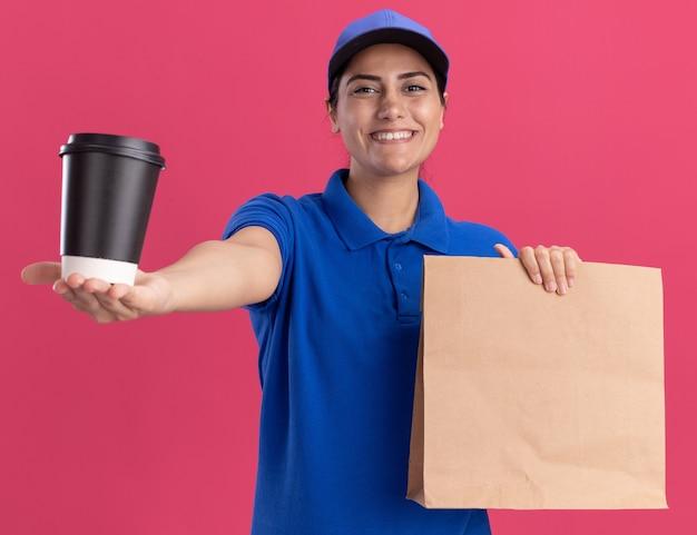 Uśmiechnięta młoda dziewczyna dostawy ubrana w mundur z czapką, trzymając papierowy pakiet żywności i trzymając filiżankę kawy z przodu na białym tle na różowej ścianie
