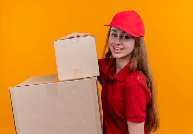 Uśmiechnięta młoda dziewczyna dostawy w czerwonym mundurze gospodarstwa pola stojące w widoku profilu na odizolowanych pomarańczowej przestrzeni