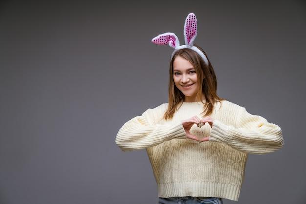 Uśmiechnięta młoda dziewczyna kaukaski, blondynka z uszami królika, pokazuje serce z dwiema rękami i patrząc na kamerę odizolowaną na szarej scenie