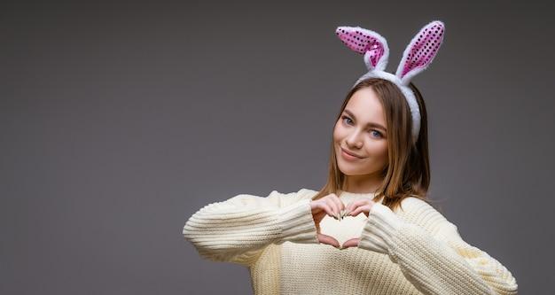 Uśmiechnięta młoda dziewczyna kaukaski, blondynka z uszami królika, pokazuje serce z dwiema rękami i patrząc na kamery na białym tle na szarym tle