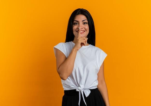 Uśmiechnięta młoda dziewczyna kaukaski gesty ciszy znak