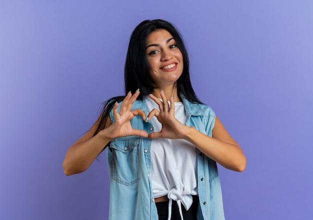 Uśmiechnięta młoda dziewczyna kaukaski gestykuluje znak ręką serca na białym tle na fioletowym tle z miejsca na kopię