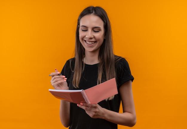 Uśmiechnięta młoda dziewczyna kaukaski na sobie czarną koszulkę, patrząc na notes w ręku na na białym tle pomarańczowy