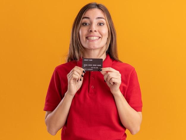 Uśmiechnięta młoda dziewczyna kaukaski posiada kartę kredytową na pomarańczowo