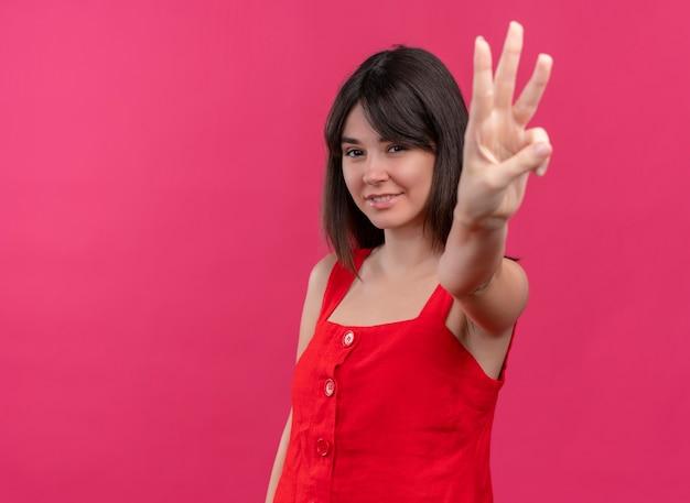 Uśmiechnięta młoda dziewczyna kaukaski robi gest trzech palców patrząc na kamery na na białym tle różowym tle z miejsca na kopię