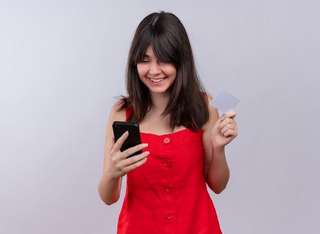 Uśmiechnięta młoda dziewczyna kaukaski trzymając telefon i kartę patrząc na telefon na na białym tle z miejsca kopiowania