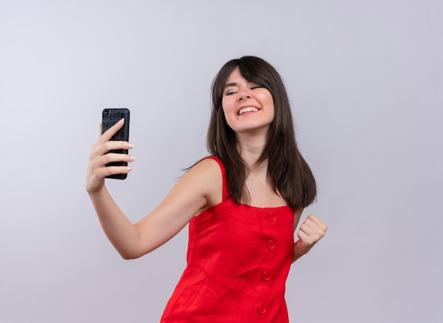 Uśmiechnięta młoda dziewczyna kaukaski trzymając telefon i podnosząc pięść patrząc na kamery na na białym tle