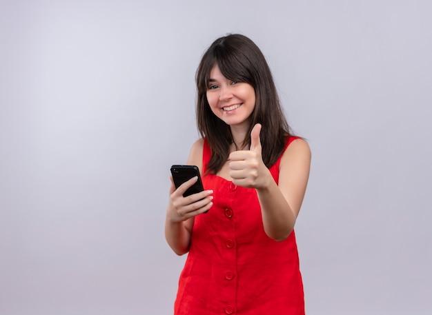 Uśmiechnięta młoda dziewczyna kaukaski trzymając telefon i robi kciuki do góry gest patrząc na kamery na na białym tle z miejsca kopiowania