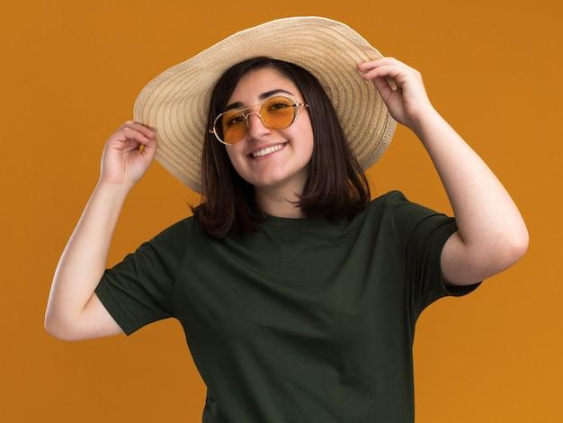 Uśmiechnięta młoda dziewczyna kaukaski w okulary przeciwsłoneczne i kapelusz plażowy na białym tle na pomarańczowej ścianie z miejsca na kopię