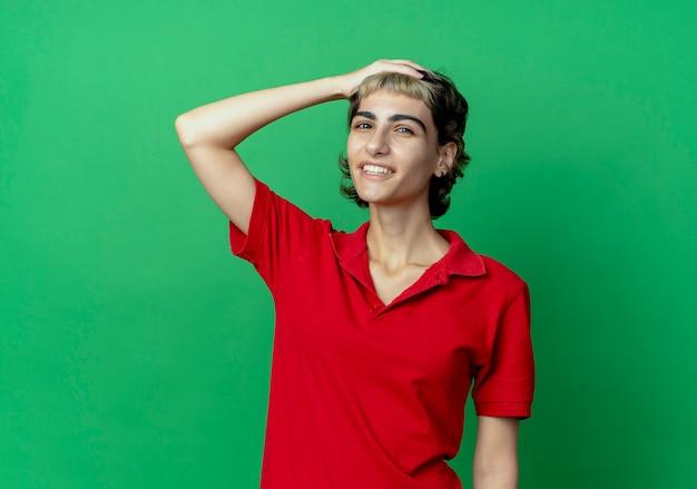 Uśmiechnięta młoda dziewczyna kaukaski z fryzurą pixie kładąc rękę na głowie na białym tle na zielonym tle z miejsca na kopię