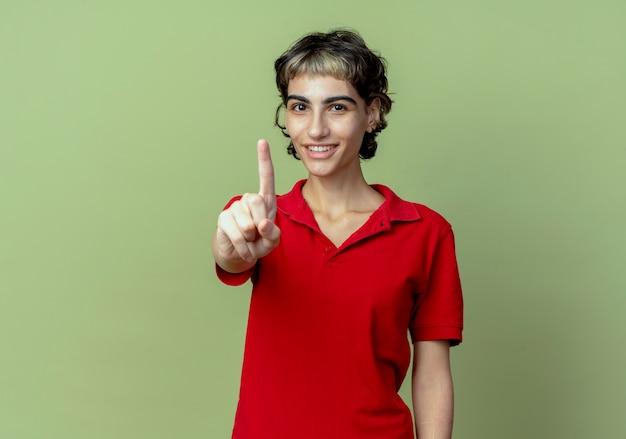 Uśmiechnięta młoda dziewczyna kaukaski z fryzurą pixie, pokazując jedną ręką w aparacie na białym tle na oliwkowozielonym tle z miejsca na kopię