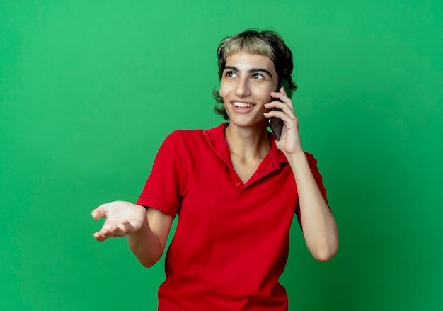 Uśmiechnięta młoda dziewczyna kaukaski z fryzurą pixie rozmawia przez telefon patrząc z boku na białym tle na zielonym tle z miejsca na kopię