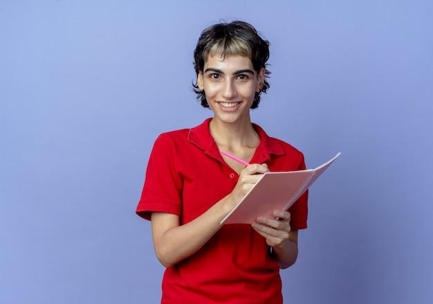 Uśmiechnięta młoda dziewczyna kaukaski z fryzurą pixie, trzymając pióro i notes, pisząc coś na białym tle na fioletowym tle z miejsca na kopię