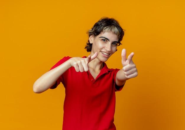Uśmiechnięta młoda dziewczyna kaukaski z fryzurą pixie, wskazując na aparat na białym tle na pomarańczowym tle z miejsca na kopię