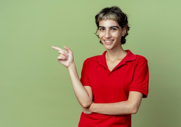 Uśmiechnięta młoda dziewczyna kaukaski z fryzurą pixie, wskazując na bok na białym tle na oliwkowym tle z miejsca na kopię