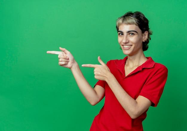 Uśmiechnięta młoda dziewczyna kaukaski z fryzurą pixie, wskazując na bok na białym tle na zielonym tle z miejsca na kopię