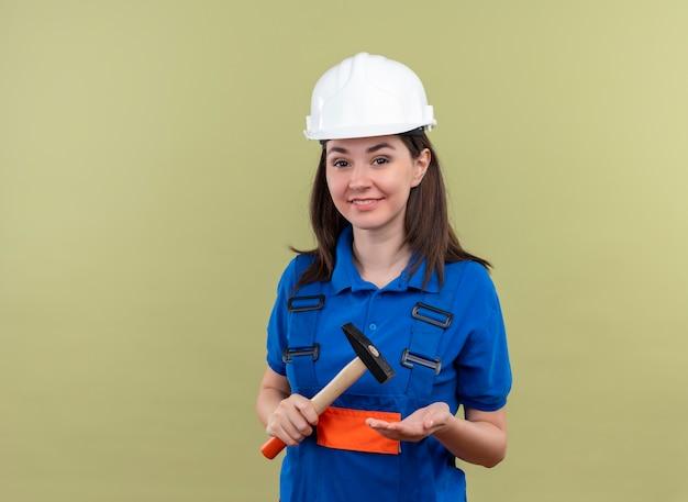 Uśmiechnięta młoda dziewczyna konstruktora w białym hełmie i niebieskim mundurze trzyma młotek i patrzy na kamerę na odosobnionym zielonym tle z miejsca na kopię
