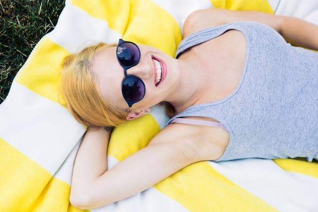 Uśmiechnięta młoda dziewczyna leży na macie w okularach przeciwsłonecznych
