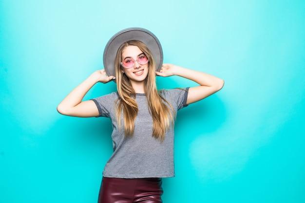 Uśmiechnięta młoda dziewczyna moda t-shirt, kapelusz i okulary przezroczyste na białym tle na zielonym tle
