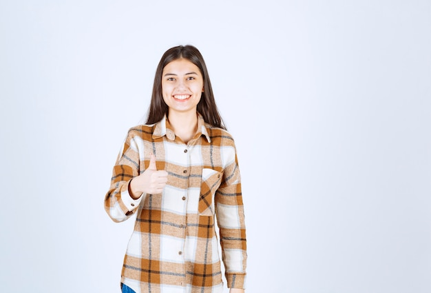 Uśmiechnięta młoda dziewczyna model pokazując kciuk do góry.