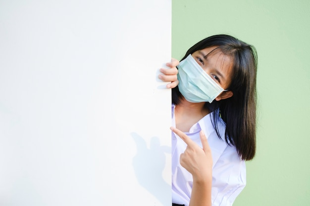 Uśmiechnięta młoda dziewczyna nosi maskę z zieloną ścianą tablicy ogłoszeń. azjatycka dziewczyna