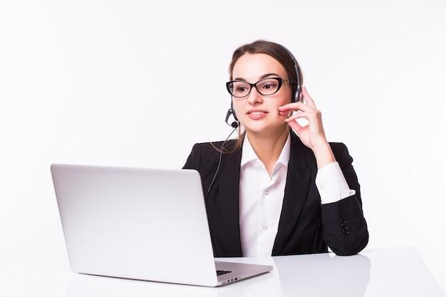 Uśmiechnięta młoda dziewczyna obsługi klienta z zestawem słuchawkowym w jej miejscu pracy na białym tle