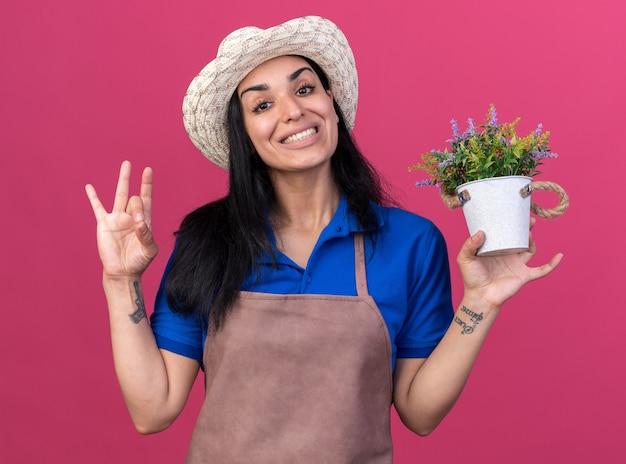 Uśmiechnięta młoda dziewczyna ogrodniczka w mundurze i kapeluszu trzymająca doniczkę, patrząca z przodu, robiąca znak ok na różowej ścianie