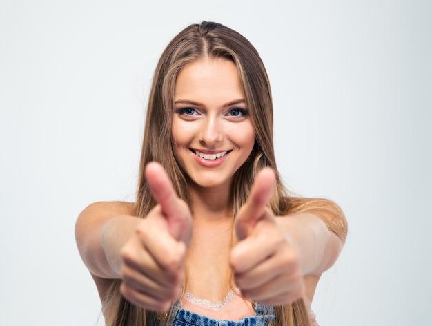 Uśmiechnięta młoda dziewczyna pokazuje aprobaty
