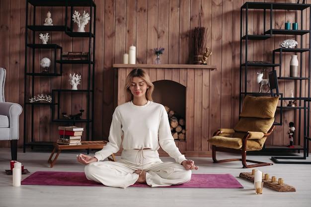 Uśmiechnięta młoda dziewczyna praktykuje jogę siedząc w pozycji lotosu, medytując w przytulnym wnętrzu domu. trening kobiet dla dobrego samopoczucia.